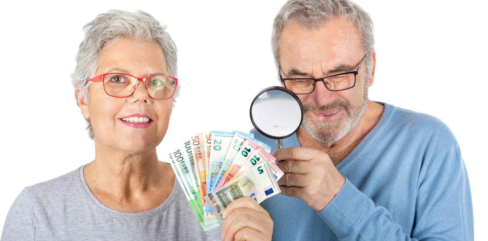 Seniorenpaar mit Geld und Lupe